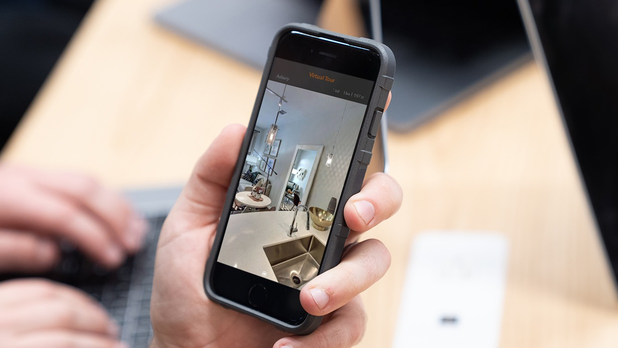 A person's hand holding a phone with a virtual tour of an apartment on the screen.