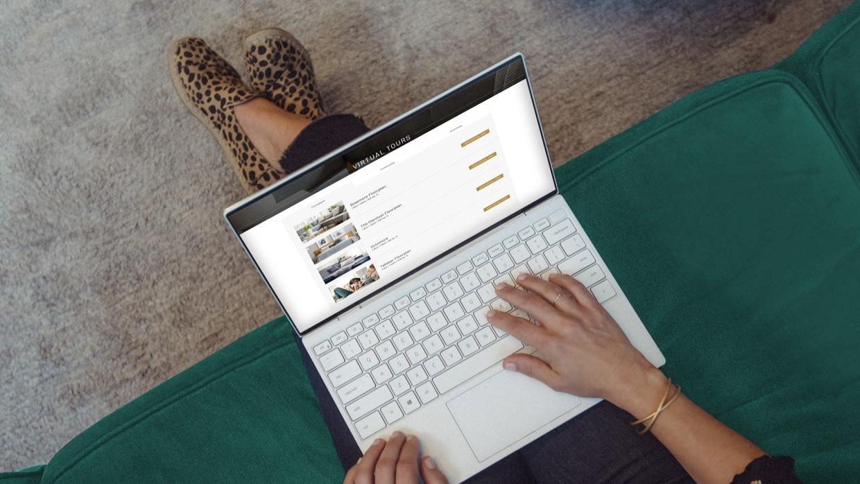Woman on laptop computer browsing through an apartment communities online virtual tours.